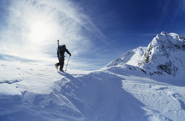 Skier hiking to mountain summit