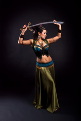 Attractive bellydancer in tribal costume and holding sword