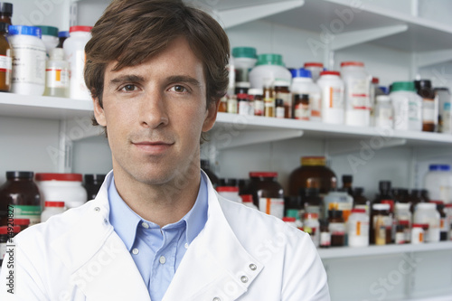 Male lab worker standing, pill bottles behind