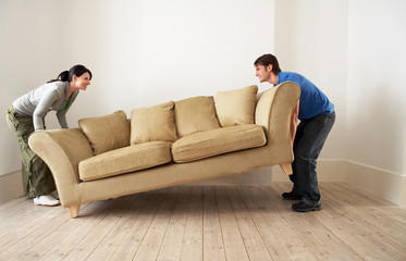 Couple lifting sofa in empty room