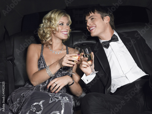 Couple in back of car drinking champagne