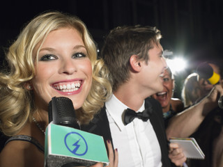 Woman talking into microphone, man behind with paparazzi