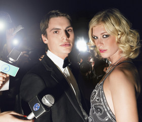 Couple posing in front of paparazzi
