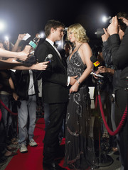 Couple embracing on red carpet