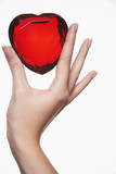 Woman holding up heart-shaped jewel between finger and thumb, close-up of hand