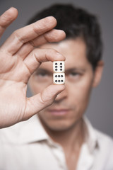 Man holding dice between finger and thumb, focus on foreground