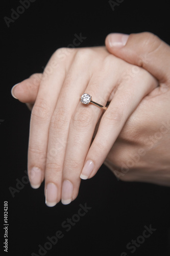 Man holding woman's hand displaying engagement ring, close up of hand