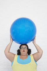 Overweight Woman Holding Exercise Ball on head
