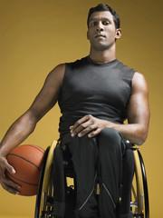 Paraplegic athlete sitting in wheelchair holding basketball
