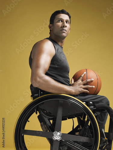 Paraplegic athlete sitting in wheelchair holding basketball, side view