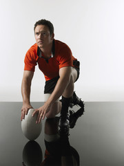 Rugby player kneeling on one knee holding ball