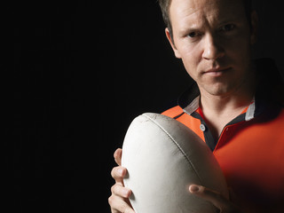 Rugby player holding ball, close-up, portrait