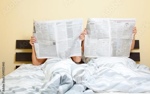 Leinwanddruck Bild couple newspaper in bed