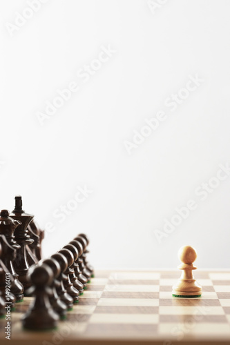 Chess game, single white piece in front of black pieces