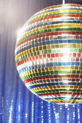 Multi-coloured disco ball in front of blue stage curtain, cropped