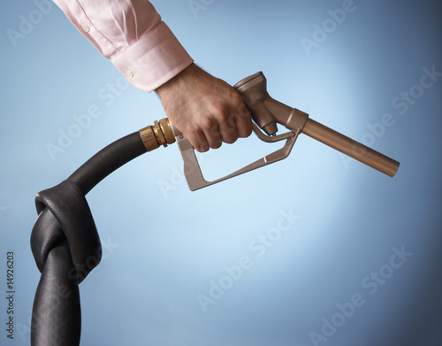Man holding fuel pump with knot in pipe, close up of hand
