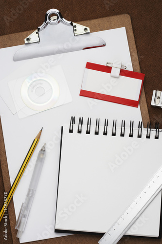 Clipboard, notepad, pencil and other office equipment arranged in studio