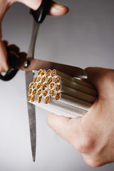 Man cutting bundle of cigarettes in half, close up of hand