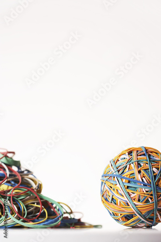 Rubber Band Ball by pile of rubber bands, in studio
