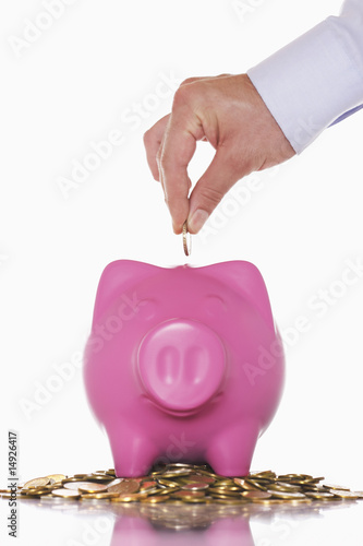 Man putting money in overflowing piggy bank, close up of hand