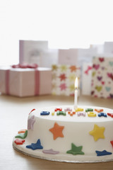 Decorated birthday cake with candle in front of cards in studio
