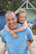 Father giving daughter piggyback on beach, portrait