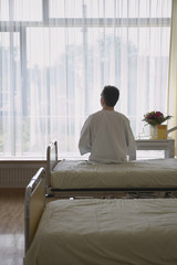 Patient Sitting on Hospital Bed, back view