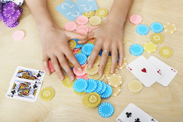 Hands of woman Grabbing Gambling Chips on table, close up of hands, overhead view