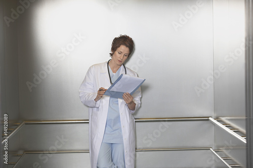 Physician Reviewing Notes in elevator