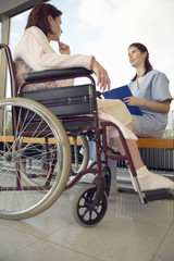 Nurse talking to patient in wheelchair, low angle view