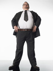 Overweight businessman standing with thumbs in belt