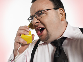 Businessman yelling into phone, close-up