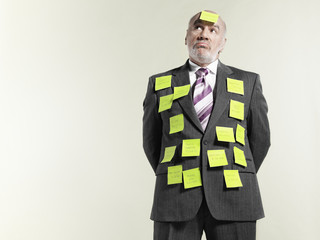 Businessman covered with sticky notes