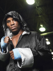 Boxer wearing robe with hood up, clenching fists, portrait