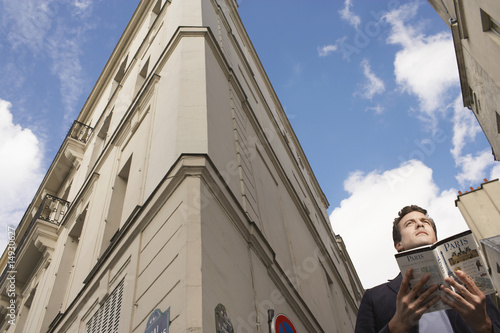 Paris, France, Man with guide book in front of apartment blocks