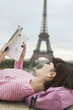 France, Paris, Young woman reading book on balcony with Eiffel Tower in distance