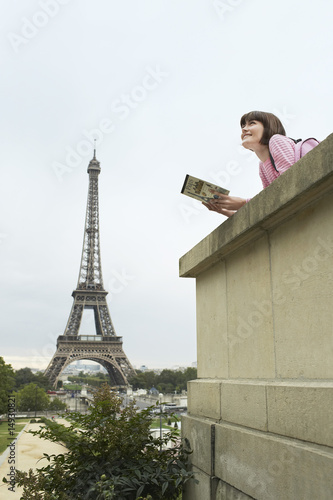 France, Paris, Young woman reading book on balcony in front of Eiffel Tower