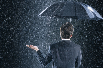 Businessman staying dry under umbrella during downpour, back view