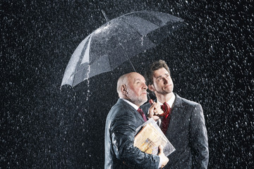 Businessmen Watching Rain from Under Umbrella