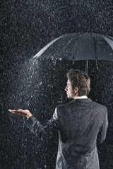 Businessman sticking hand out from under umbrella to feel rain, back view