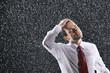 Businessman running hands through wet hair, standing in the Rain