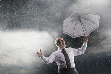 Businessman holding umbrella, Laughing in Storm, low angle view