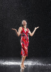 Woman, arms raised, smiling, standing in rain