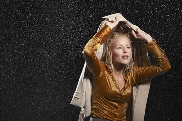 Businesswoman covering head with jacket during rainstorm