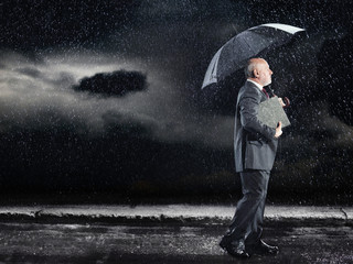 Businessman Walking in rain under umbrella, side view