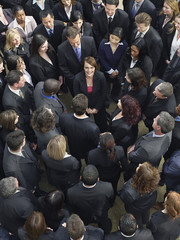 Large group of business people surrounding woman looking up, elevated view