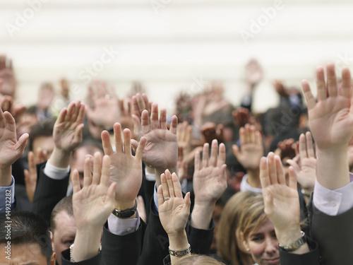 Crowd of people raising hands, focus on hands
