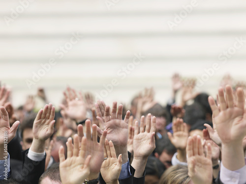 Crowd of people raising hands, focus on hands