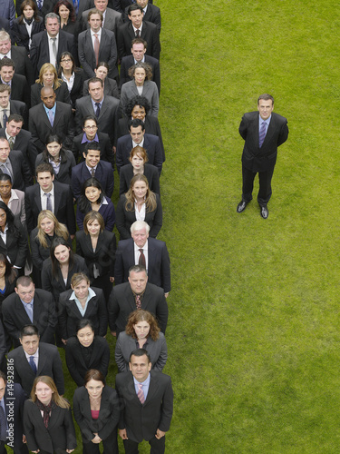 Business man standing next to large group of business people in formation, elevated view, portrait