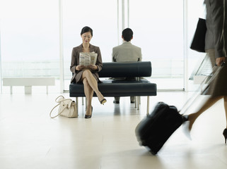 Businesswoman sitting on bench in airport, reading newspaper